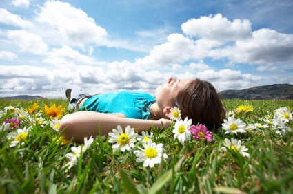 Photo to illustrate the relaxing effects of a sedation dentistry. A young woman is lying on her back in a field of flowers. A blue sky full of clouds is above her.