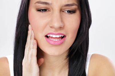 Photo of a young brunette woman with her hand on the right side of her face, for information about emergency dentistry from Baton Rouge dentist Dr. Steven Brooksher.
