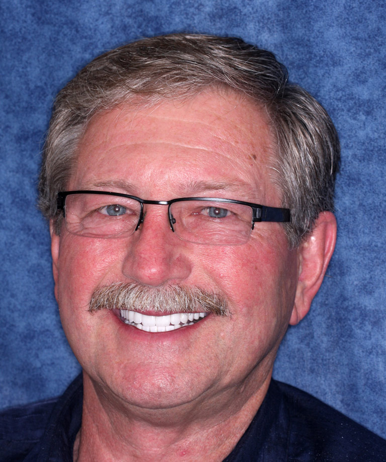 Headshot photo of Nick smiling showing smile makeover results from Dr. Brooksher