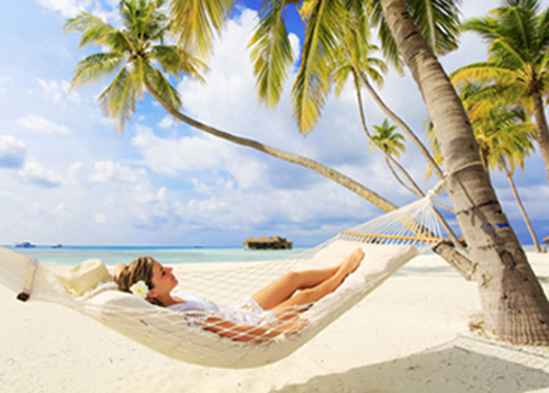 Photo of a young woman relaxing in a hammock that is tied to palm trees on the beach; for information on Baton Rouge sedation dentistry from Dentistry by Brooksher.